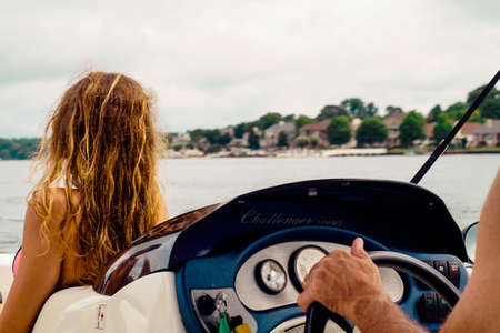 Dirty Blonde Girl Looking out over the Lake on a Speed Boat Stock Photo
