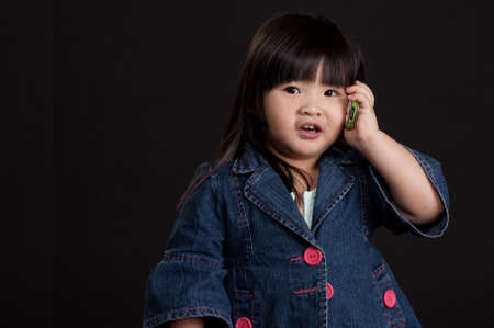 Cute little chinese girl using mobile phone photo