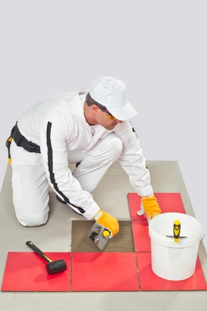 tile adhesive: Worker Applies Tile Adhesive with Notched Trowel Tile on a Floor