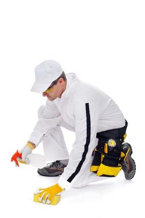 pulizia pavimenti: lavoratore pulisce il pavimento con una spugna e spray