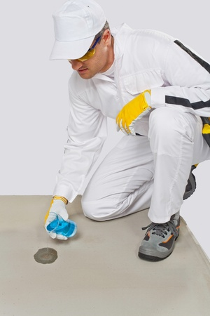 humidity: Worker with glass flask of water testing the humidity of cement base Stock Photo