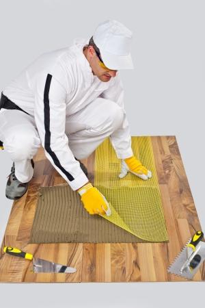 applies reinforce fiber mesh on tile adhesive on wooden floor photo