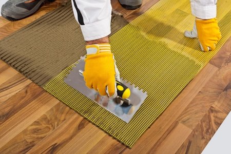 tile adhesive: applies tile adhesive on wooden floor with reinforce fiber mesh Stock Photo