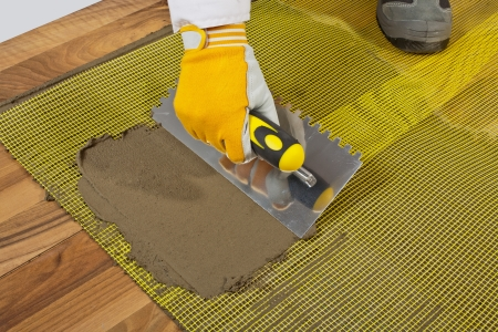 applies tile adhesive on wooden floor with reinforcement mesh
