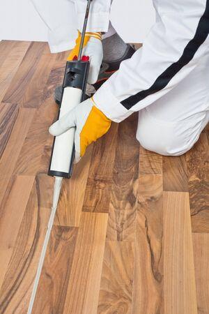 penetracion: Appling sellador de silicona en los espacios de piso de madera vieja