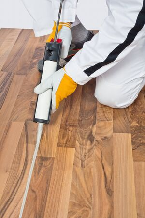 Appling silicone sealant in spaces of old wooden floor Stock Photo - 14669992