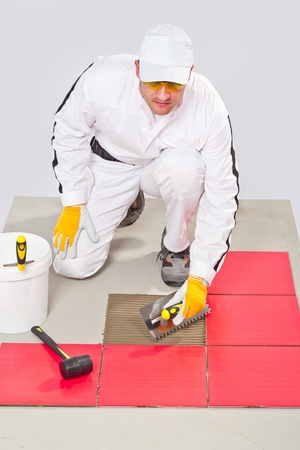 Appling Tile Adhesive with Notched Trowel on a Floor Stock Photo - 14711125