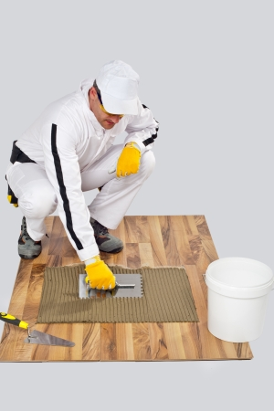 tile adhesive: Appling Tile Adhesive with Notched Trowel on a old wood Floor Stock Photo