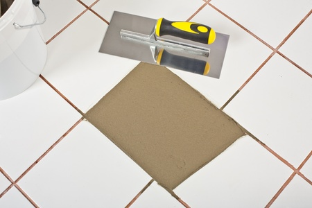 tile adhesive: bucket and Trowel and old white tiles with tile adhesive
