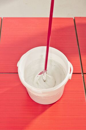 tile grout: bucket with mixed grout ready to fill joint on tiles