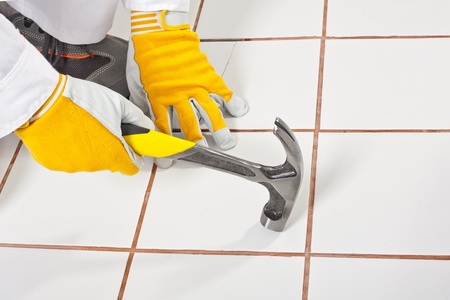 checking old tiles base with hammer Stock Photo