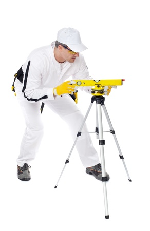 construction worker in white coveralls looking instrument level Stock Photo