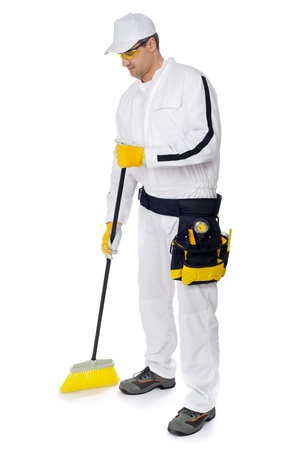 construction worker in white overalls sweeping with a broom on white background Stock Photo