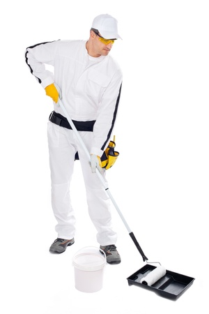 construction worker in white overalls with paint roller bucket on a white background Stock Photo