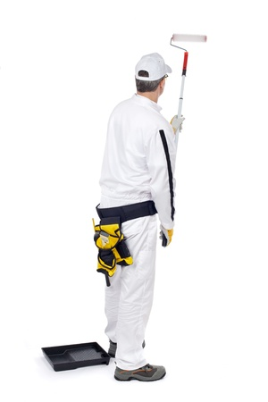 construction worker in white overalls with paint roller paint wall Stock Photo