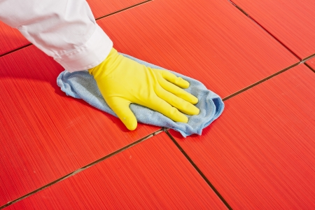 Hand with yellow gloves and blue towel clean red tiles grout Stock Photo