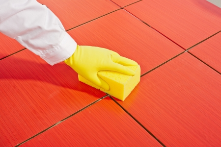 hand with yellow gloves and yellow sponge clean red tiles Stock Photo