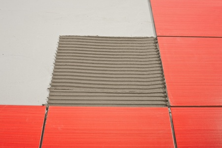 notched trowel adhesive and red tiles Stock Photo