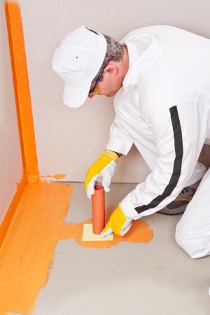 waterproofing: plumber applied waterproofing cuff on the floor of the bathroom pipe corner aqueduct channel
