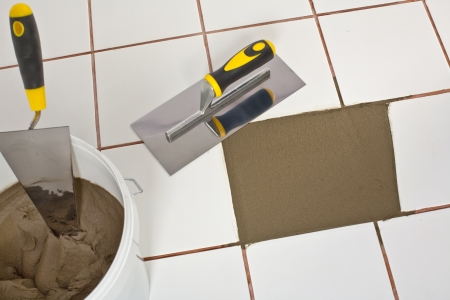 Repaired old white tiles floor with Trowel and tile adhesive Stock Photo