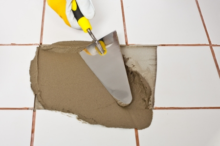tile adhesive: Repairing old white tiles with tile adhesive Stock Photo