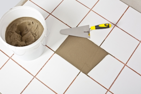 Trowel and old white tiles with tile adhesive Stock Photo
