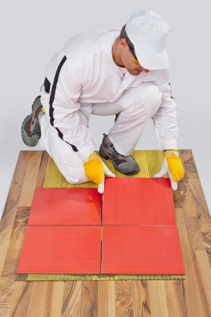 worker applies ceramic tiles on wooden floor with fiber mesh photo