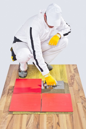 worker applies ceramic tiles on wooden floor with noched trowel photo
