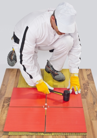 worker applies ceramic tiles on wooden floor with rubber hammer photo