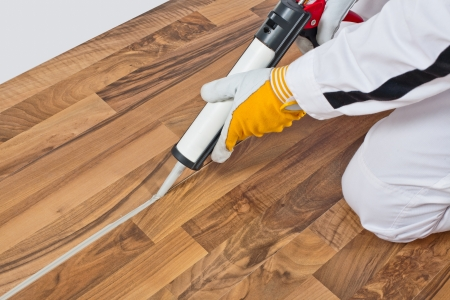 worker applies silicone sealant spaces of old wooden floor photo