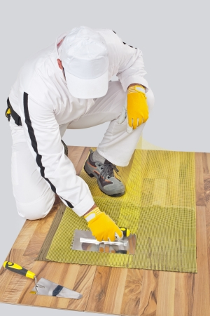 Worker applies tile adhesive on wooden floor with reinforcement mesh Stock Photo - 14669985