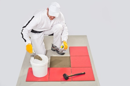 tile adhesive: Worker Applies Tile Adhesive with Notched Trowel Tile