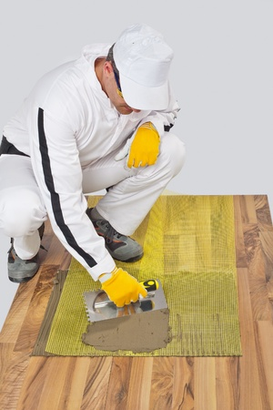 Worker applies tile adhesive with reinforcement mesh on wooden floor photo