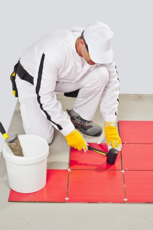 Worker Applies with Rubber Hummer Red Tile on a Floor Stock Photo - 14702733