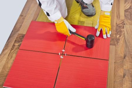 Worker Applies with Rubber Hummer Tile on a wooden Floor reinforced net