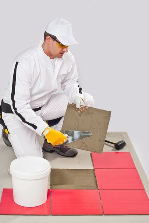 Worker Applies with Trowel Tile Adhesive on a Floor Red Tile Stock Photo - 14711952