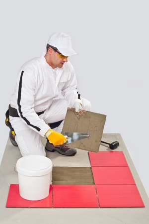 tile adhesive: Worker Applies with Trowel Tile Adhesive on a Floor Red Tile