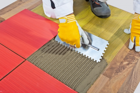 worker apply ceramic tiles on wooden floor mesh trowel Stock Photo - 14696063