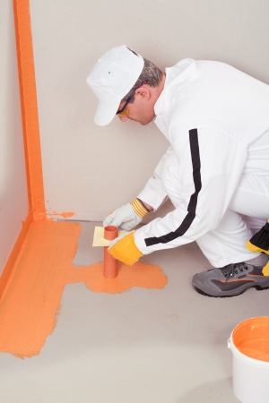 worker brush applied waterproofing on the floor of the bathroom pipe corner aqueduct channel Stock Photo - 14715755
