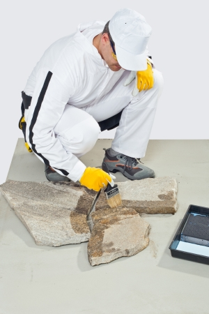 worker brush primer grout of stones Stock Photo - 14715766