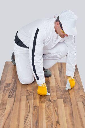 worker checks old wooden floor for cracks photo