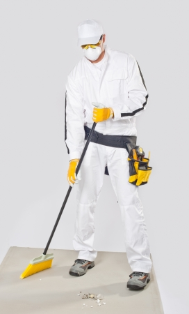 worker clean cement base with broom photo
