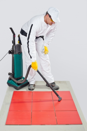 worker clean tiles on floor and joints with vacuum cleaner photo