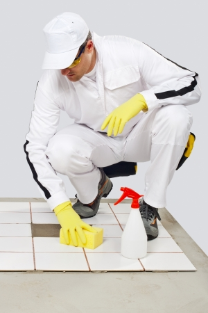 Worker cleans with sponge and spray old tiles floor before tilling and removes dirt, dust and greasy spot photo
