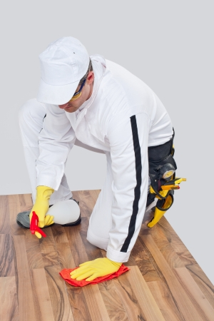 Worker cleans with sponge and spray old wooden floor before tilling and removes dirt, dust and greasy spot