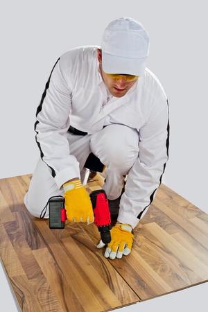 worker drilled wooden floor cracks photo