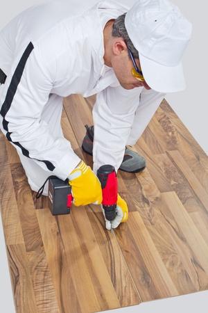 worker drills a screw wooden floor cracks photo