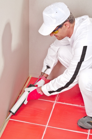 worker in white clouts lays silicone sealant corner wall floor Stock Photo