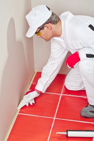 sealant: worker lays silicone sealant corner wall floor Stock Photo