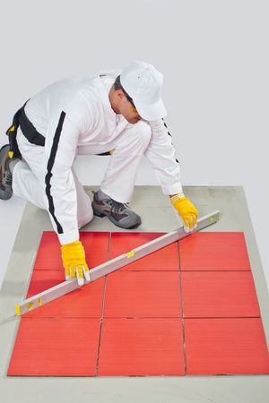 Worker levels Tiles applied on Floor reinforced fiber mesh photo